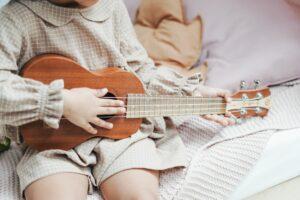 a girl holding brown ukulele