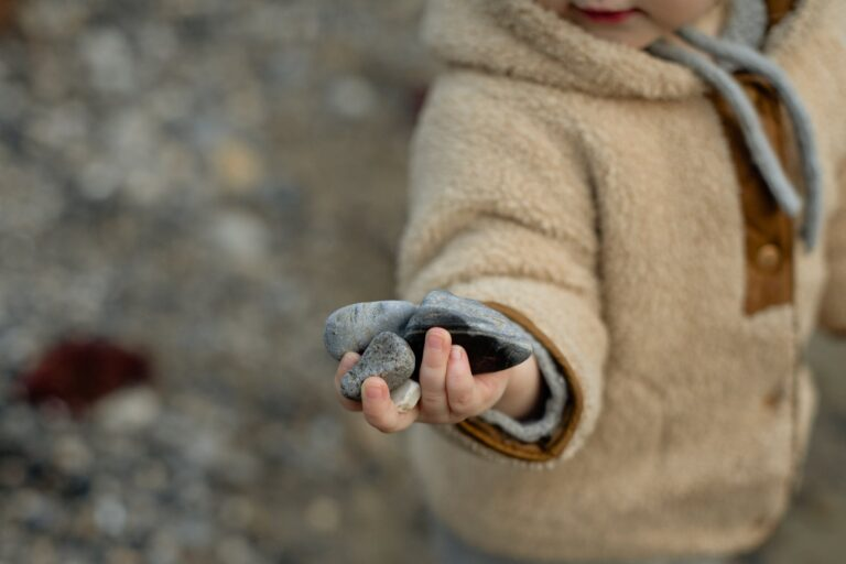 curious little kid in warm coat holding stones in hand on shore