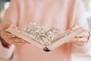 crop woman with open book and sprigs of gypsophila